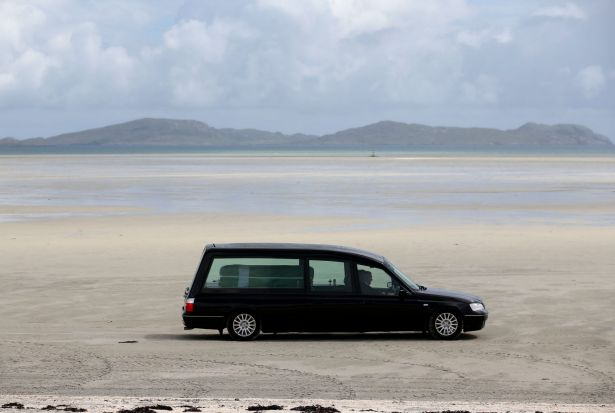 The hearse carrying the coffin of Eilidh MacLeod draped in the Barra flag is driven across Traigh Mhor beach at Barra ...