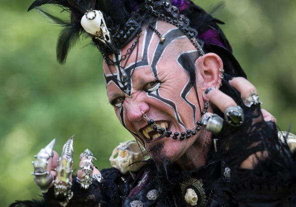 A participant of the so called 'Victorian Picnic' performs in a fancy costume during the Wave Gothic Festival (WGT) in ...