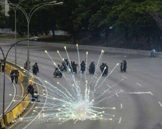 Fireworks launched by anti-government demonstrators explode near government forces in Caracas, Venezuela.