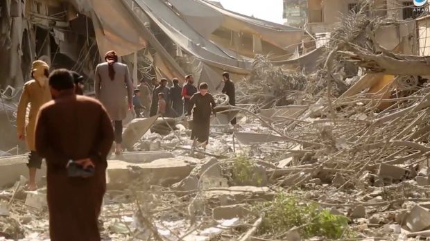Images released by Islamic State's propaganda arm purport to show people inspecting damage from airstrikes and artillery ...