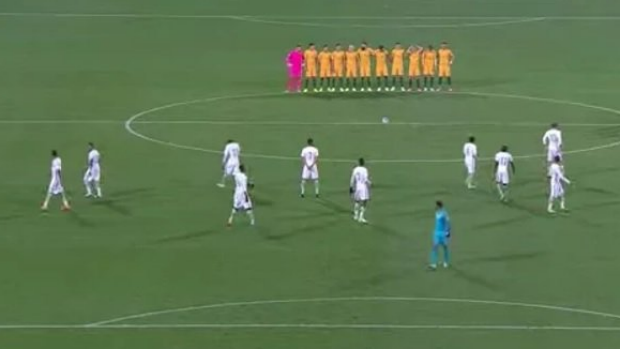 Controversial moment: The Australian players stand arm in arm in remembrance as Saudi counterparts fail to do likewise