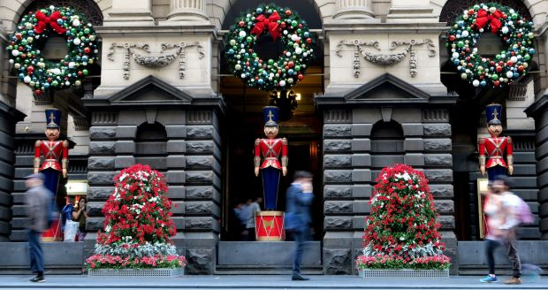Melbourne Town Hall, Christmas soldiers stand silent as pedestrians pass by.