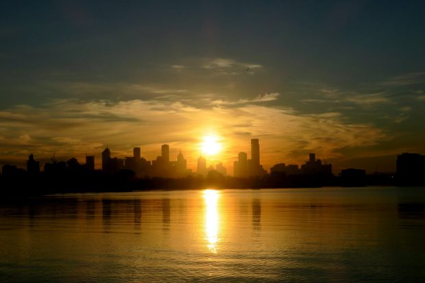 Rising sun over the city of Melbourne taken from Port Melbourne.