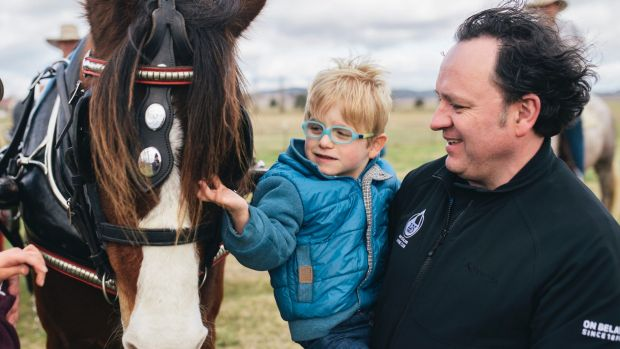 Paul Dowden and his three-year-old son Sebastian enjoy the horses on the Majura Road property Springfield on Friday.