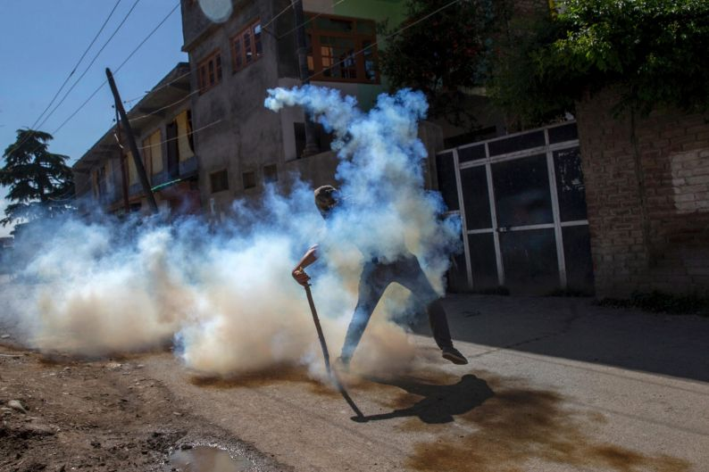 A Kashmiri protester throws back a detonated tear gas shell at Indian police during a protest in Srinagar, Indian ...