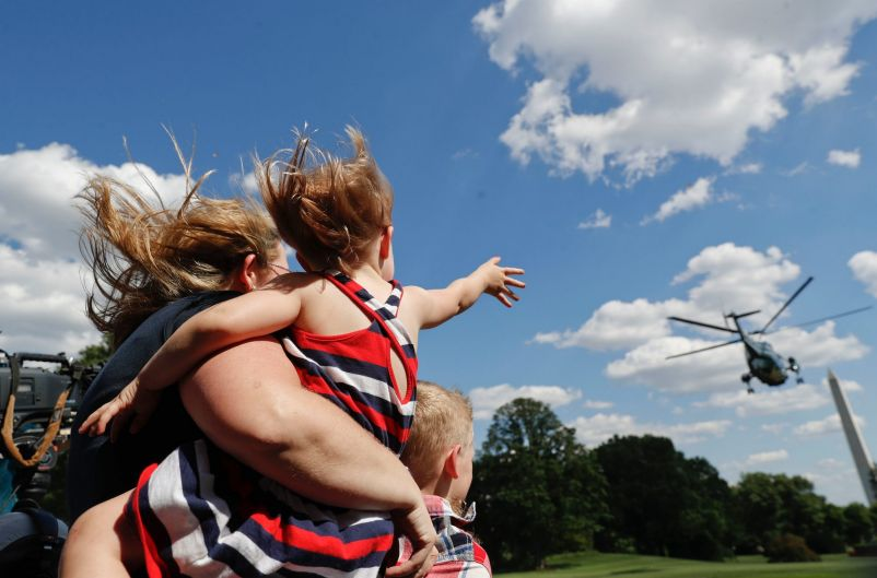 Guests and her children watch as Marine One helicopter, with President Donald Trump aboard, lift off from the South Lawn ...