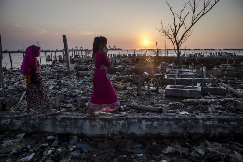 Two young girls walk through garbage as they head to the public cemetery for prayers, which is surrounded by rising sea ...