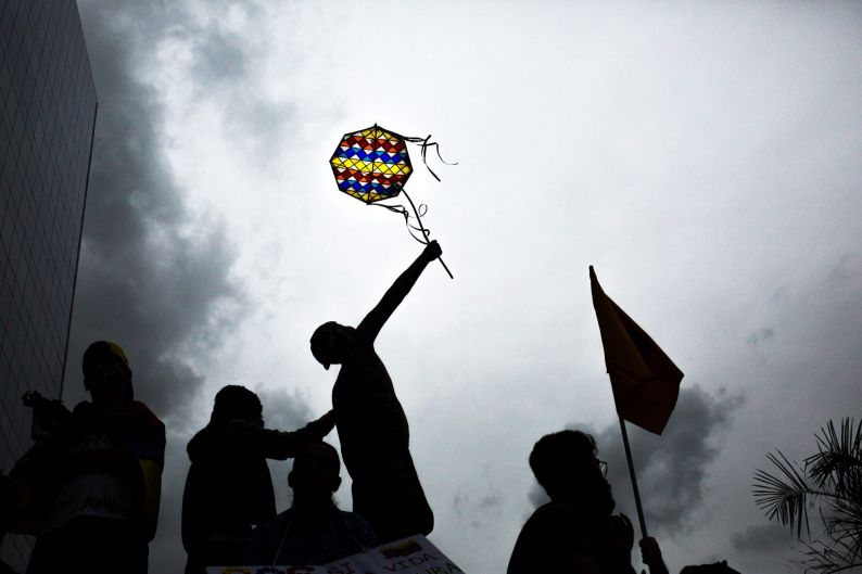 An opposition supporter holds a flag displaying the colors of the Venezuelan flag during a vigil in honor of 17 year-old ...