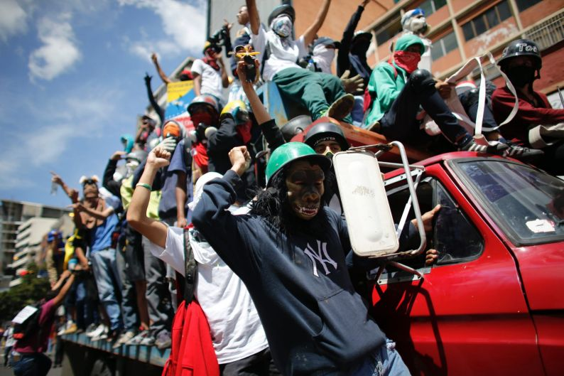 Anti-government protesters ride on a truck in Caracas, Venezuela. The protest movement against President Nicolas Maduro ...