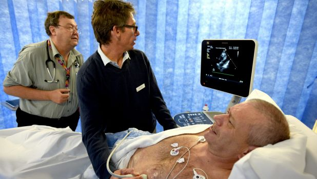 Emergency physicians Bruce Way and Matt Davis check a POCUS scan as they assess the heart of patient David McLean.