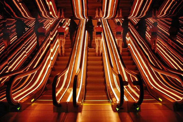 Two guests, center, and their refections as they ride an escalator in the lobby of the PUBLIC hotel on Manhattan's Lower ...