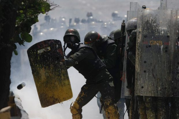 Bolivarian National Guards shield themselves from a jar thrown at them by anti-government protesters in Caracas, Venezuela.