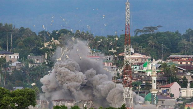 Debris flies as the Philippine Air Force bomb suspected locations of Muslim militants in Marawi Cty.