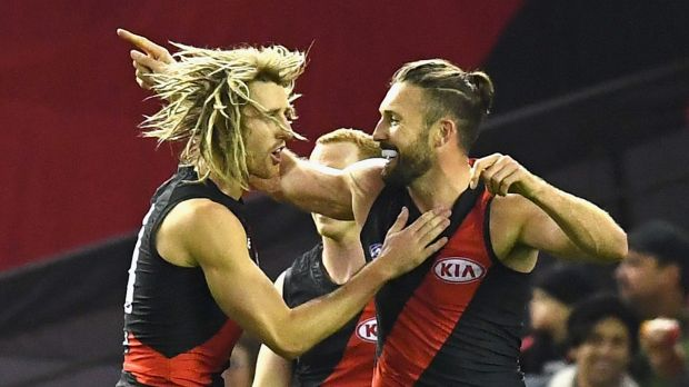 Cale Hooker (right) celebrates a goal with Dyson Heppell.