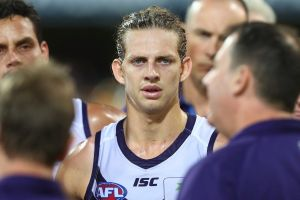 Dockers skipper Nat Fyfe looks on while coach Ross Lyon talks to players.