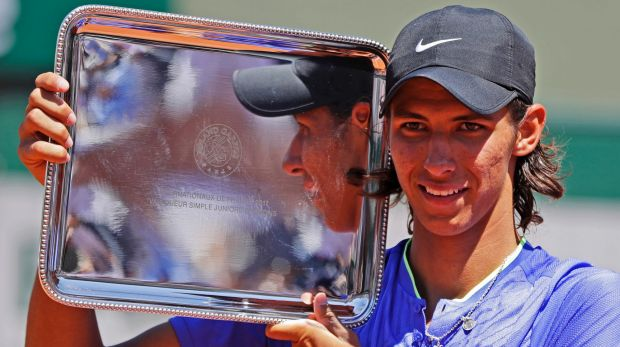 Australia's Alexei Popyrin hold the trophy after winning his boys' final match of the French Open.