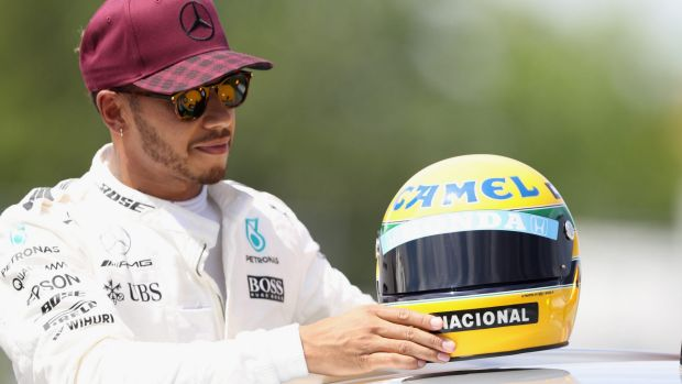 Chasing legends: Lewis Hamilton with a commemorative helmet of F1 legend Ayrton Senna after matching his record 65 pole ...