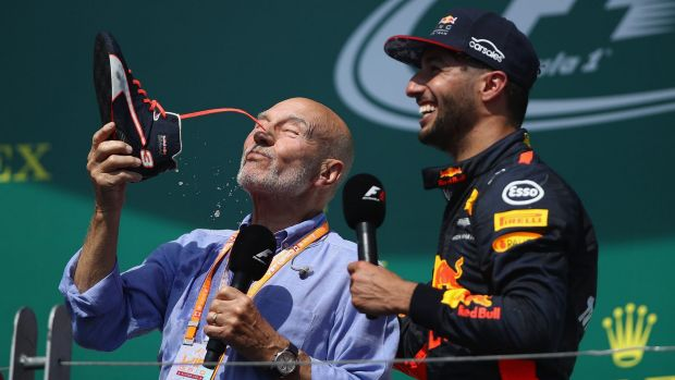Actor Patrick Stewart does a 'shoey' on the podium with Daniel Ricciardo.