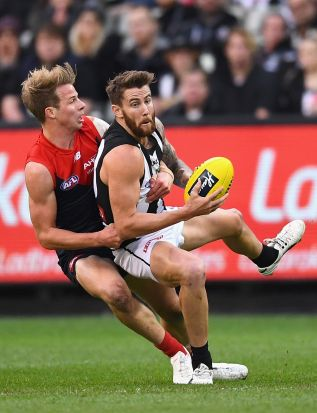 MELBOURNE, AUSTRALIA - JUNE 12: Jeremy Howe of the Magpies is tackled by Mitch Hannan of the Demons during the round 12 ...