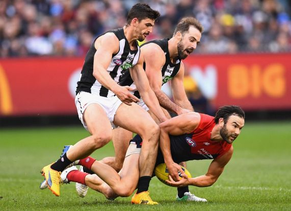 MELBOURNE, AUSTRALIA - JUNE 12: Jordan Lewis of the Demons is tackled by Scott Pendlebury and Steele Sidebottom of the ...