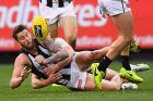 MELBOURNE, AUSTRALIA - JUNE 12: Jeremy Howe of the Magpies handballs whilst being tackled by Mitch Hannan of the Demons ...