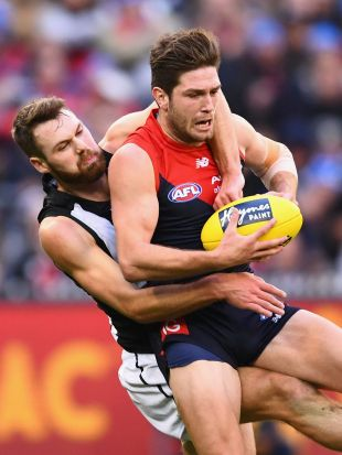 Tomas Bugg of the Demons marks infront of Matthew Scharenberg of the Magpies during the round 12 AFL match between the ...