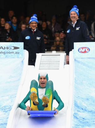 MELBOURNE, AUSTRALIA - JUNE 12: Steve Moneghetti goes down the Freeze MND slide during the round 12 AFL match between ...