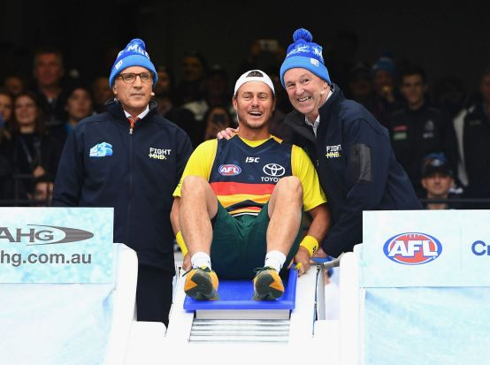 MELBOURNE, AUSTRALIA - JUNE 12: Lleyton Hewitt prepares to go down the Freeze MND slide during the round 12 AFL match ...