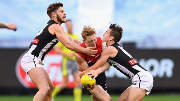Clayton Oliver of the Demons is tackled by Taylor Adams and Callum Brown of the Magpies.