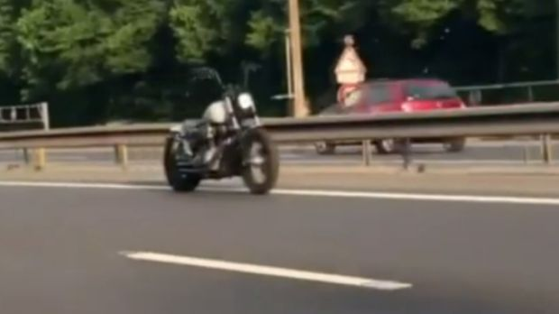The riderless motorcycle cruising along the motorway.