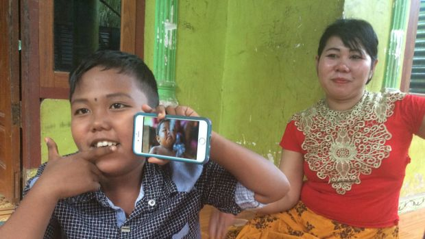 Aldi Rizal, with his mother Diana, quit smoking when he was four. He is holding up a YouTube video of his younger ...