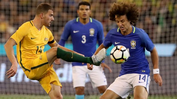 Under pressure: Socceroo James Troisi tries to get a kick away from Brazil's David Luiz.