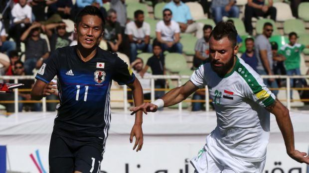 Japan's Yuya Kubo, left, and Iraq's Waleed Salim Al-Lami compete for the ball.