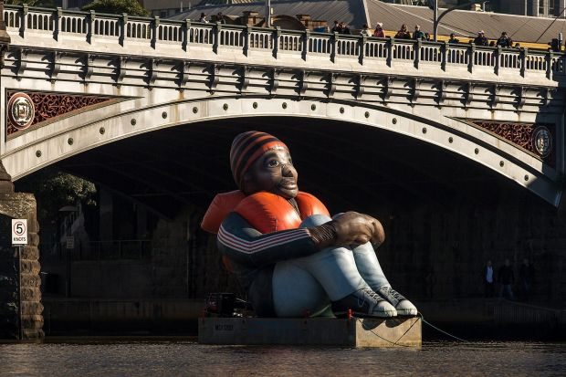 Inflatable Refugee floats along the Yarra River before it is temporarily installed at Melbourne's Immigration Museum.