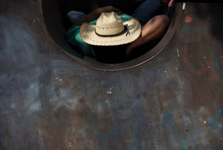 "A protester rests inside a piece of public art as he awaits the start of an ""anti-imperialist"" protest decrying U.S. ..."