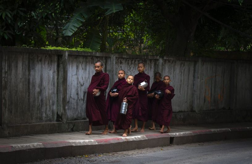 "Buddhist monks walk to collect their morning ""alms"" (offerings) in Yangon, Myanmar."
