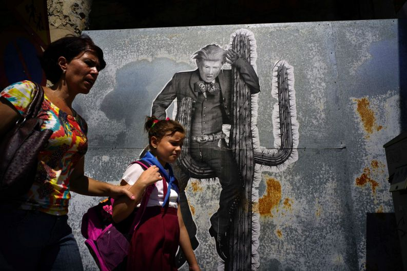 A woman walks with her daughter past a mural painting depicting U.S. President Donald Trump in Havana, Cuba.