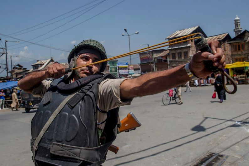 An Indian paramilitary soldier uses a sling to shoot glass marbles at Kashmiri protesters in Srinagar, Indian controlled ...