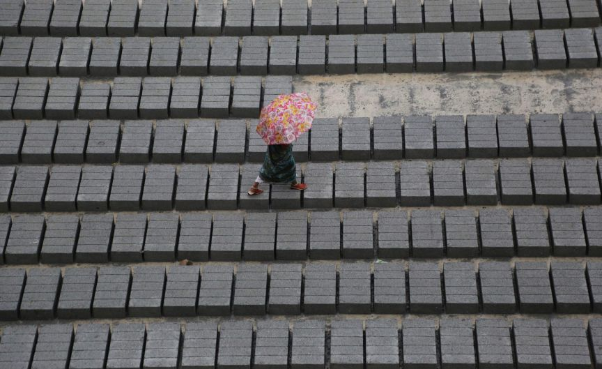 An Indian woman holds an umbrella and walks over cement blocks arranged in rows as it rains in Bangalore, India.