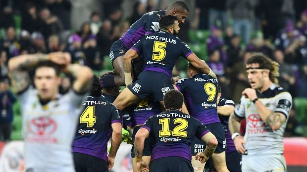 Brodie Croft is swamped by his Melbourne Storm teammates after kicking the winning goal against the Cowboys.