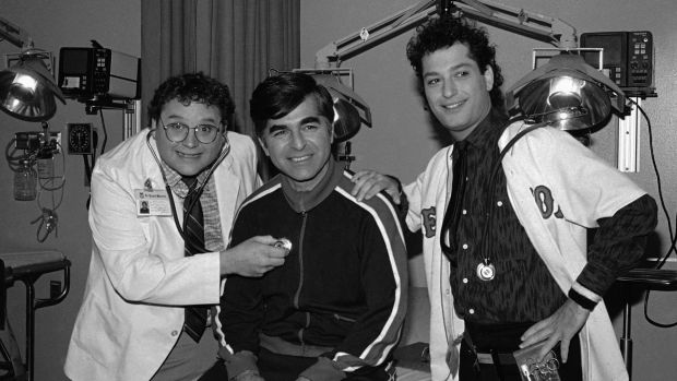 1984: Massachusetts Govenor Michael Dukakis, center, receives treatment from Stephen Furst, left, and Howie Mandel, ...