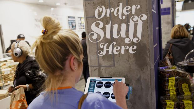 A customer uses a tablet computer to place an order at the new Whole Foods Market in Los Angeles.