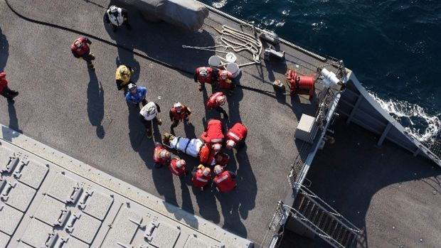 US military personnel prepare to transfer an injured person from the USS Fitzgerald.