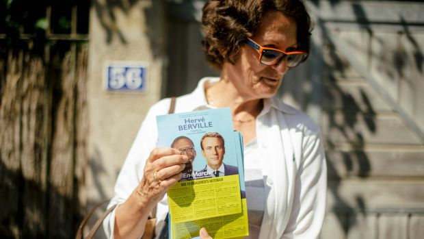 A supporter of Herve Berville, a candidate with the new La Republique en Marche party, holds a flyer at a market in St ...