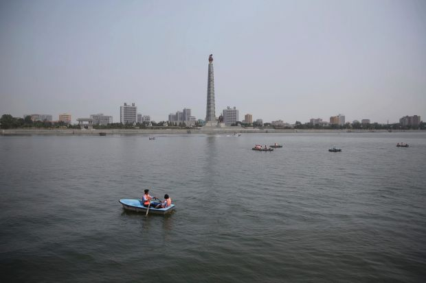 North Koreans row boats on the Taedong River against a backdrop of the Juche Tower, Sunday, June 18, 2017, in Pyongyang, ...