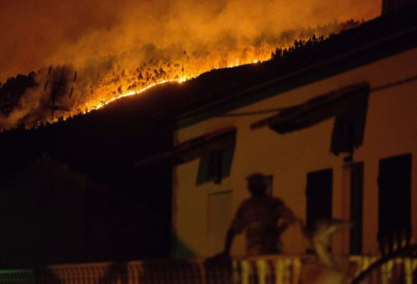 A man on the balcony of a house looks up at a forest fire raging on a hillside above the village of Avelar, central ...