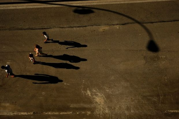 Shadows of people are cast on the street as the sun sets, in Pamplona, northern Spain, Saturday June 17, 2017.