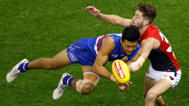 Committed: Bulldog Lin Jong goes in hard against Melbourne's Tomas Bugg.