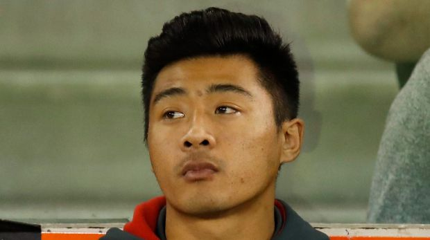 Sidelined: Lin Jong looks on after injuring his knee against the Demons.