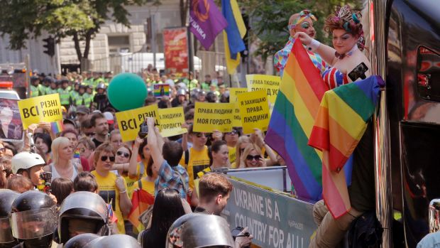 Gay and lesbian rights activists demonstrate during the annual Gay Pride parade, being protected by riot police in Kiev, ...